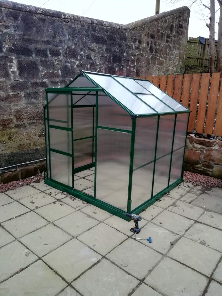 A green framed greenhouse